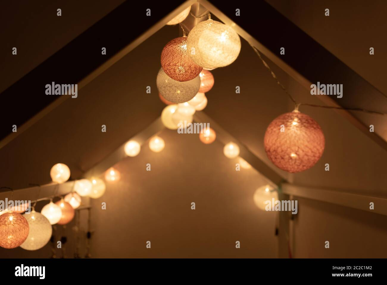 Roof shaped bed canopy decorated in montessori room with bright light garland illuminating dark bedroom in evening at home Stock Photo