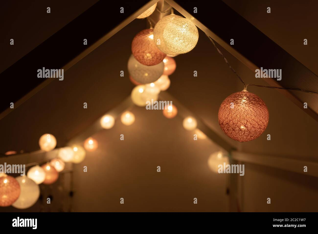 Roof Shaped Bed Canopy Decorated In Montessori Room With Bright Light Garland Illuminating Dark Bedroom In Evening At Home Stock Photo Alamy