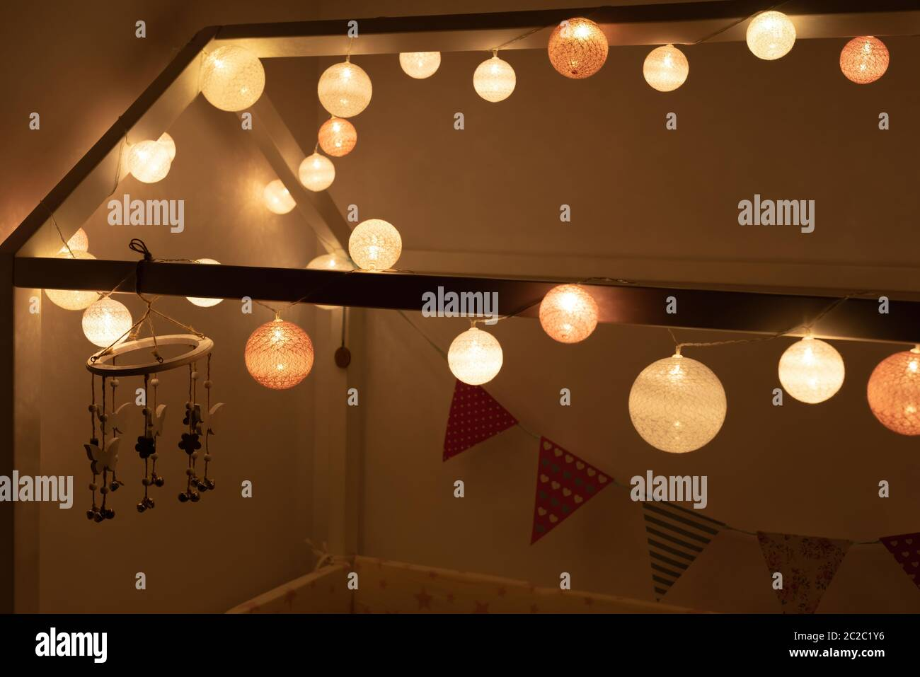 Bright light garland wrapped around canopy of bed in montessori room in evening in cozy bedroom Stock Photo