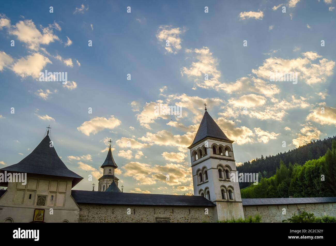 From below aged towers of Putna Orthodox Monastery located against cloudy morning sky in Romania Stock Photo