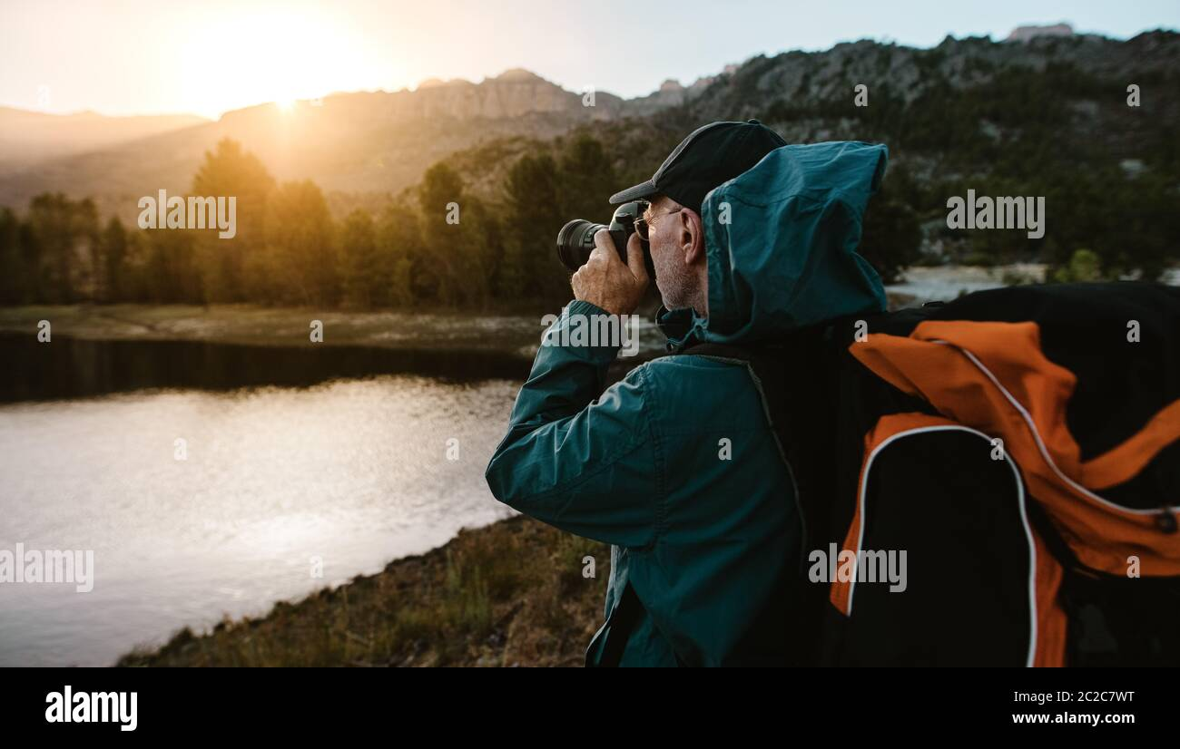 Senior man on hiking trip taking photographs of the view with a digital camera. Man hiker standing by the river in forest and taking photos. Stock Photo
