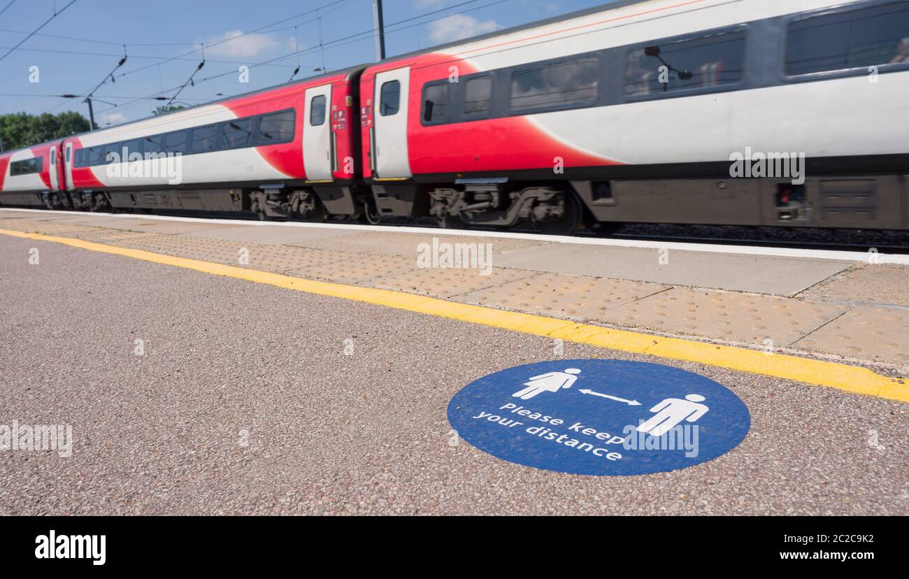 Marking on a railway station platform asking people to respect the 2 metre social distancing rule due to the coronavirus pandemic in June 2020, UK. Stock Photo