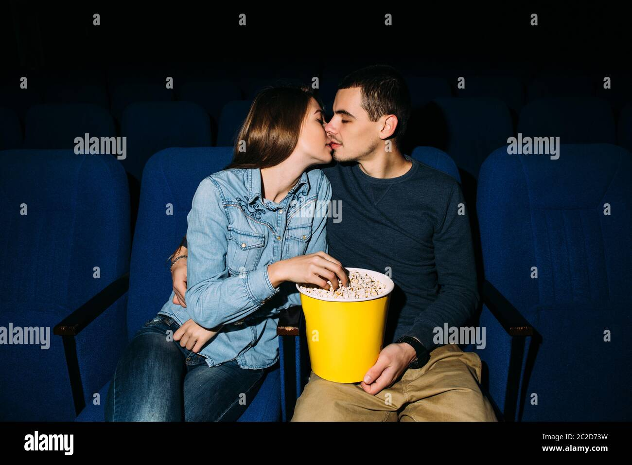 Cinema day. Young beautiful couple kissing while watching romantic