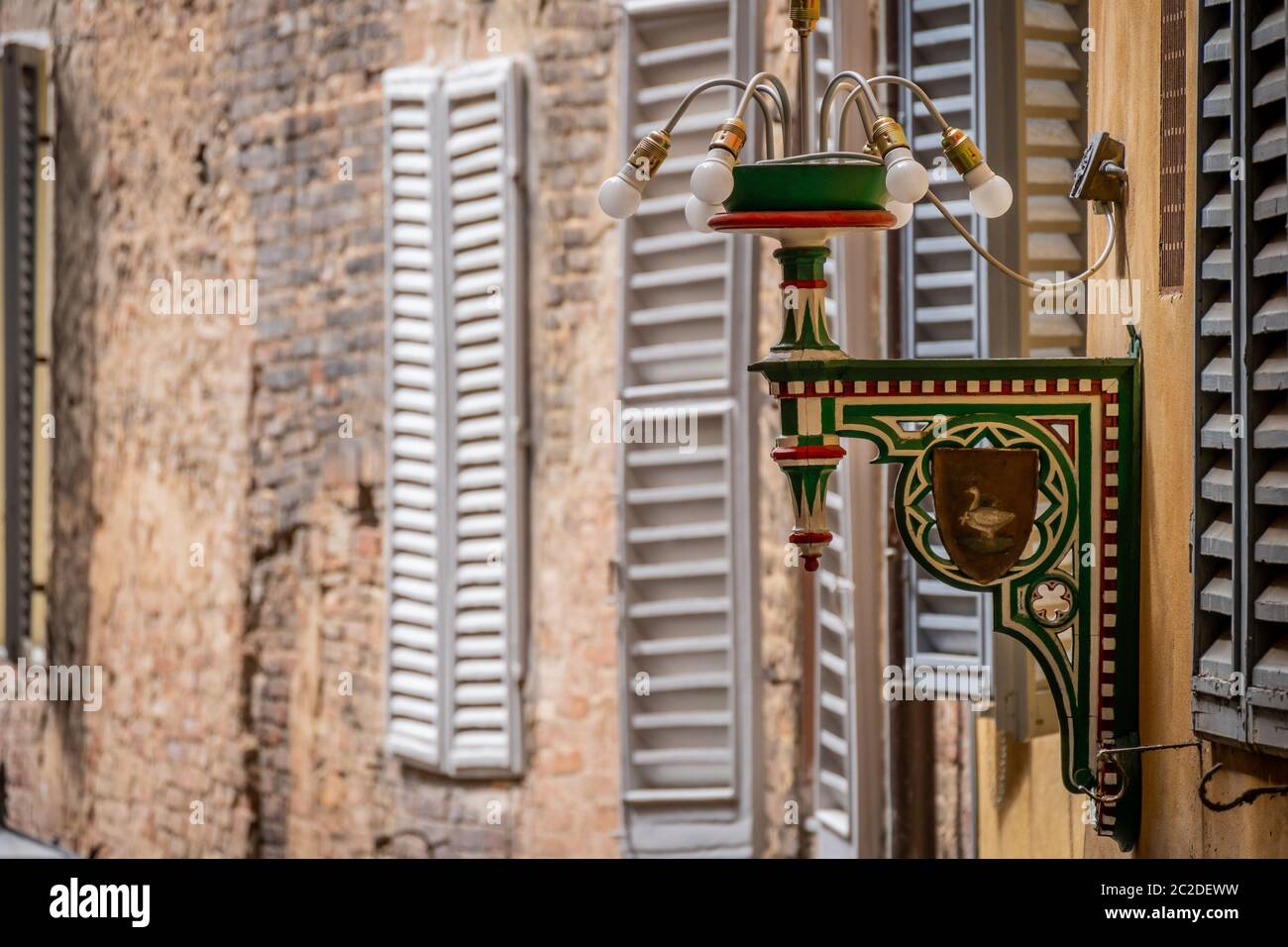Siena, Italy, April 2018: Street Lamp of the goose district in Siena. Tuscany, Italy. Each colour and shape marks one specific territory which belongs to one specific Contrada. High quality photo Stock Photo