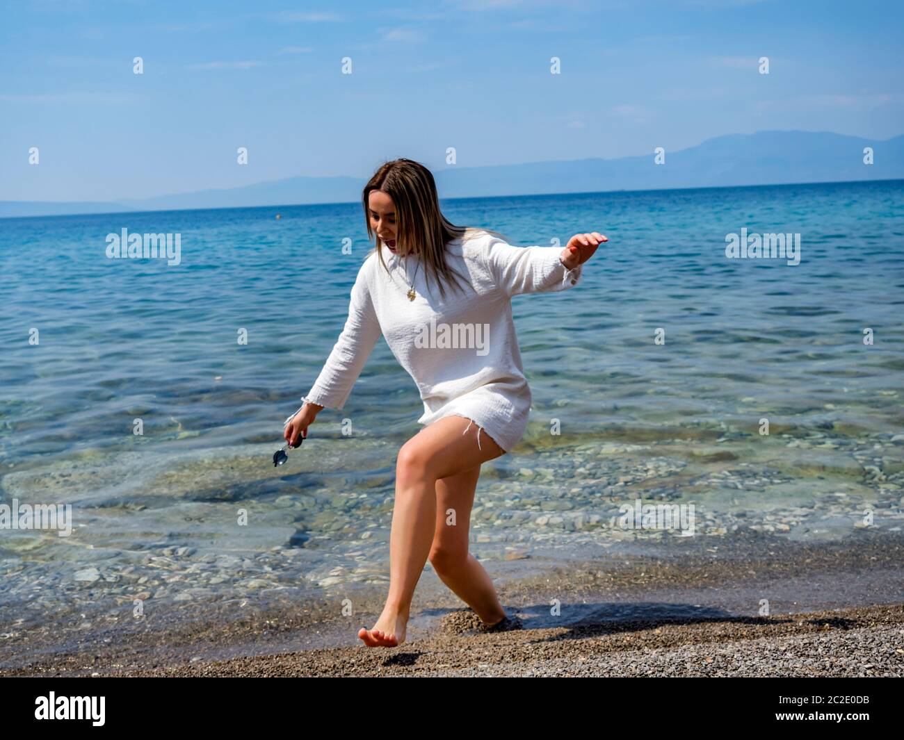Teengirl rushing out of water sea because of cold chill sandy sand beach Stock Photo