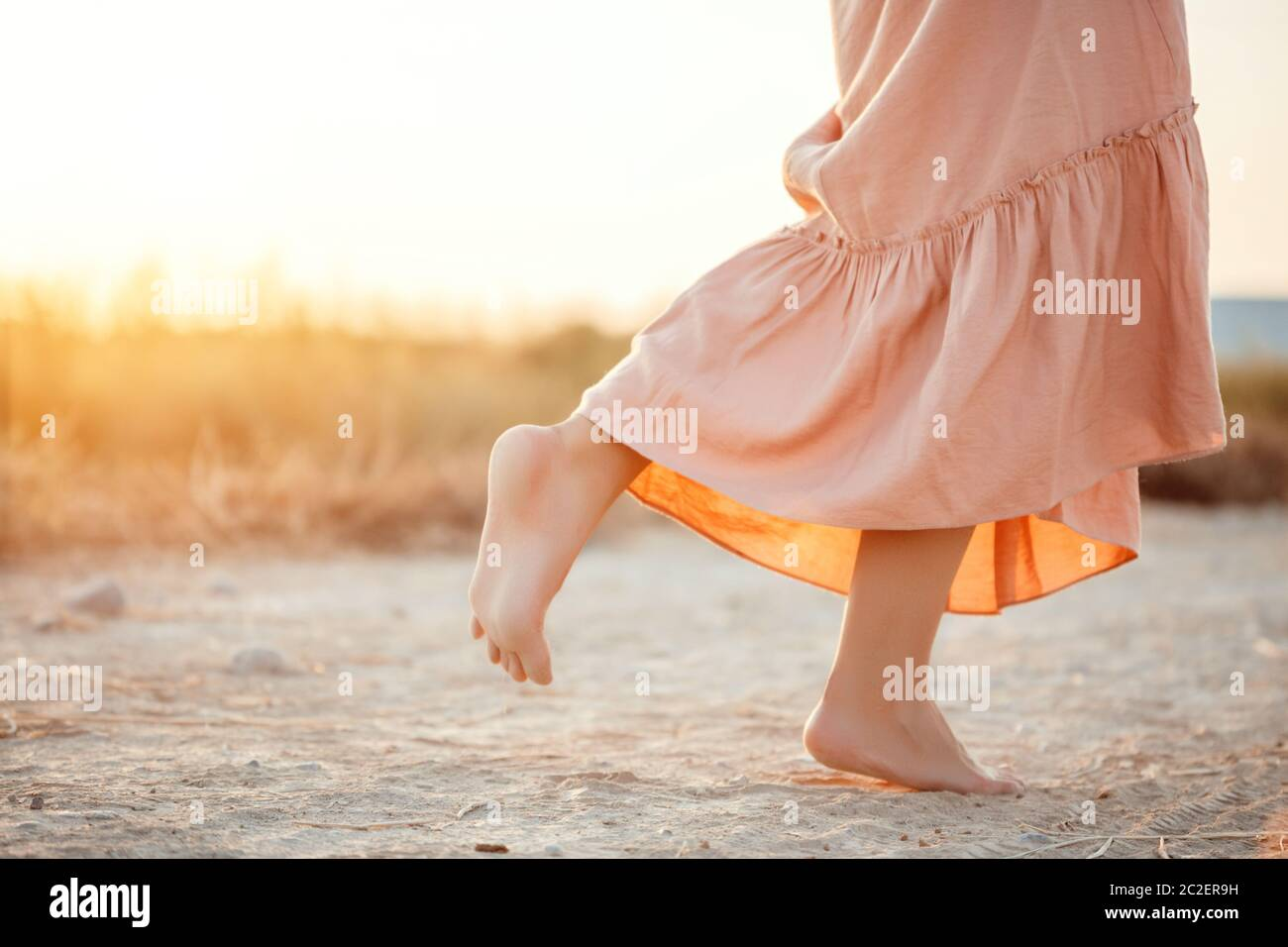 feet of a woman in a pink dress walking on the sand during sunset Stock Photo