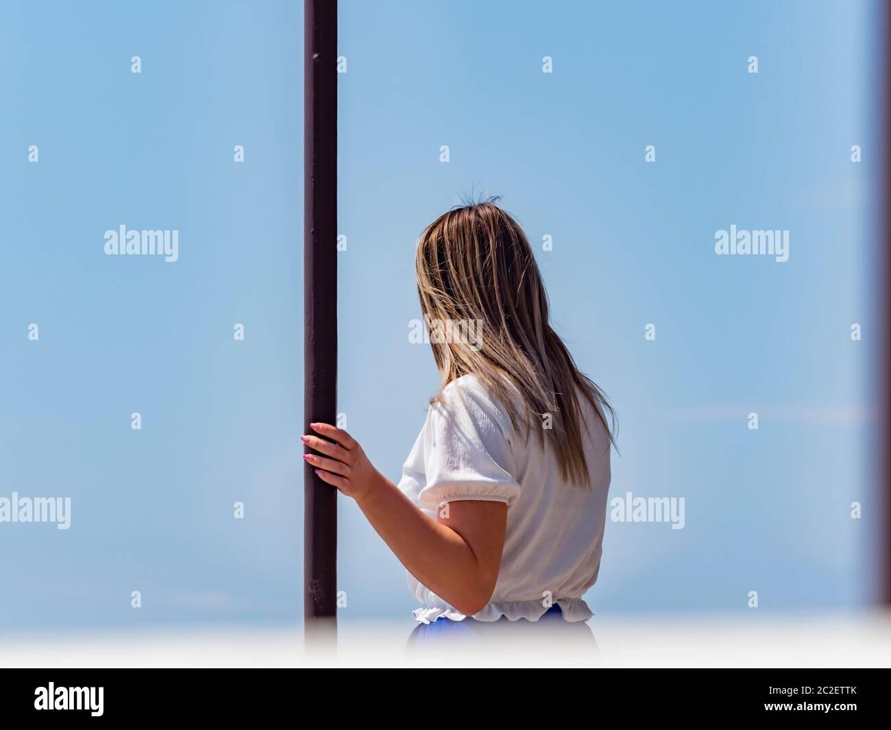 Teengirl hand holding metal post column Stock Photo