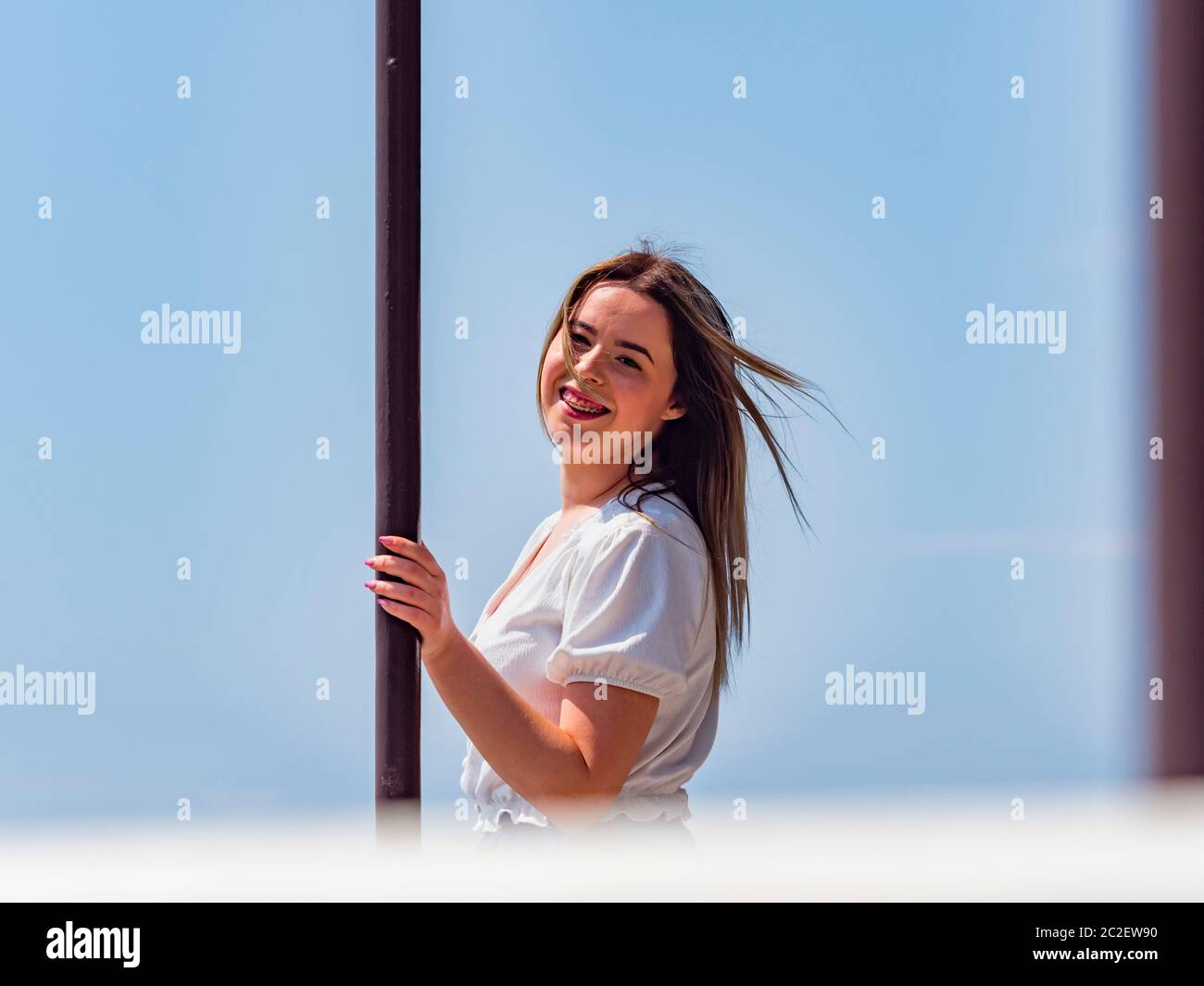Teengirl spontaneous with teeth braces looking at camera ey eyes contact eyeshot hand holding metal post column Stock Photo
