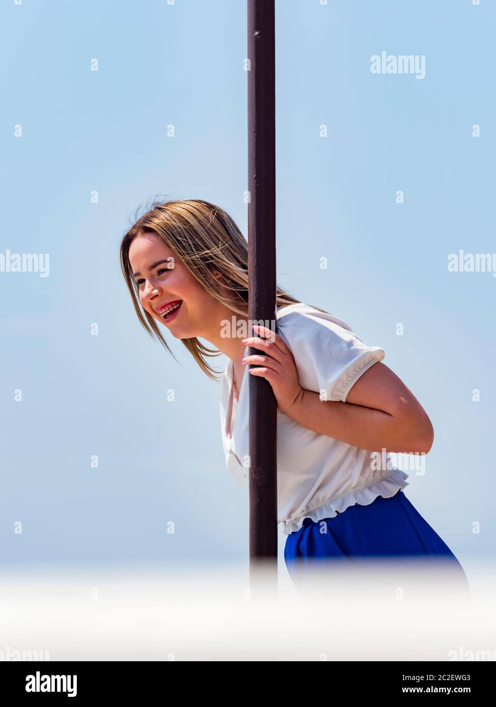 Teengirl spontaneous with teeth braces laughing squinting eyes looking away hand holding metal post column Stock Photo