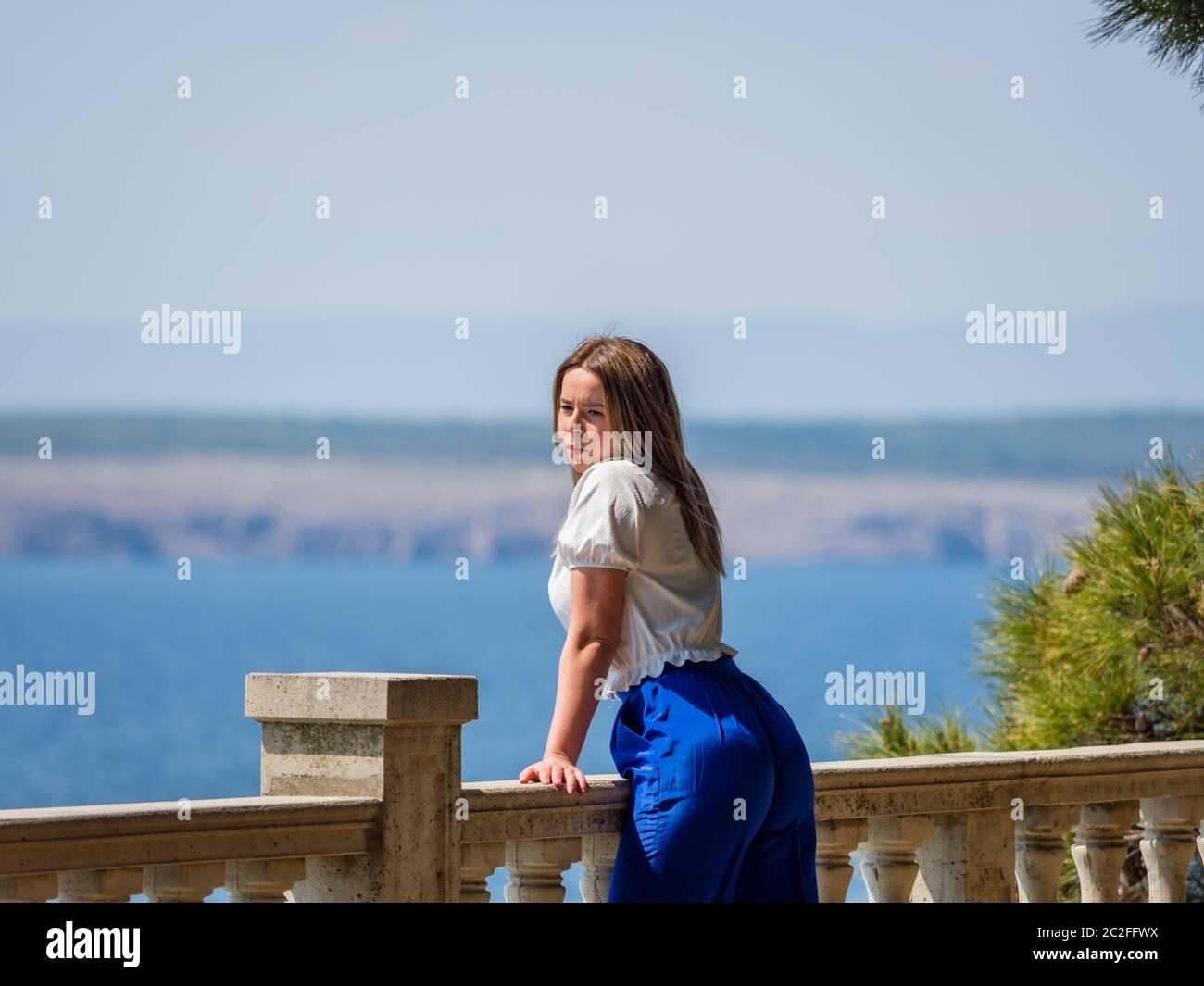 Teengirl standing by fence overlooking sea seaside looking away watching on watch looking at camera eyeshot eye eyes contact Stock Photo