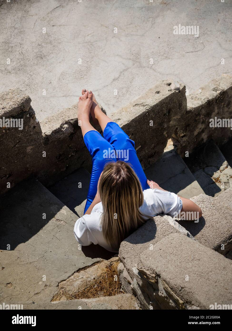 Teengirl seated sitting on staircase steps stairs view from above barefeet barefoot bare-feet legs Stock Photo