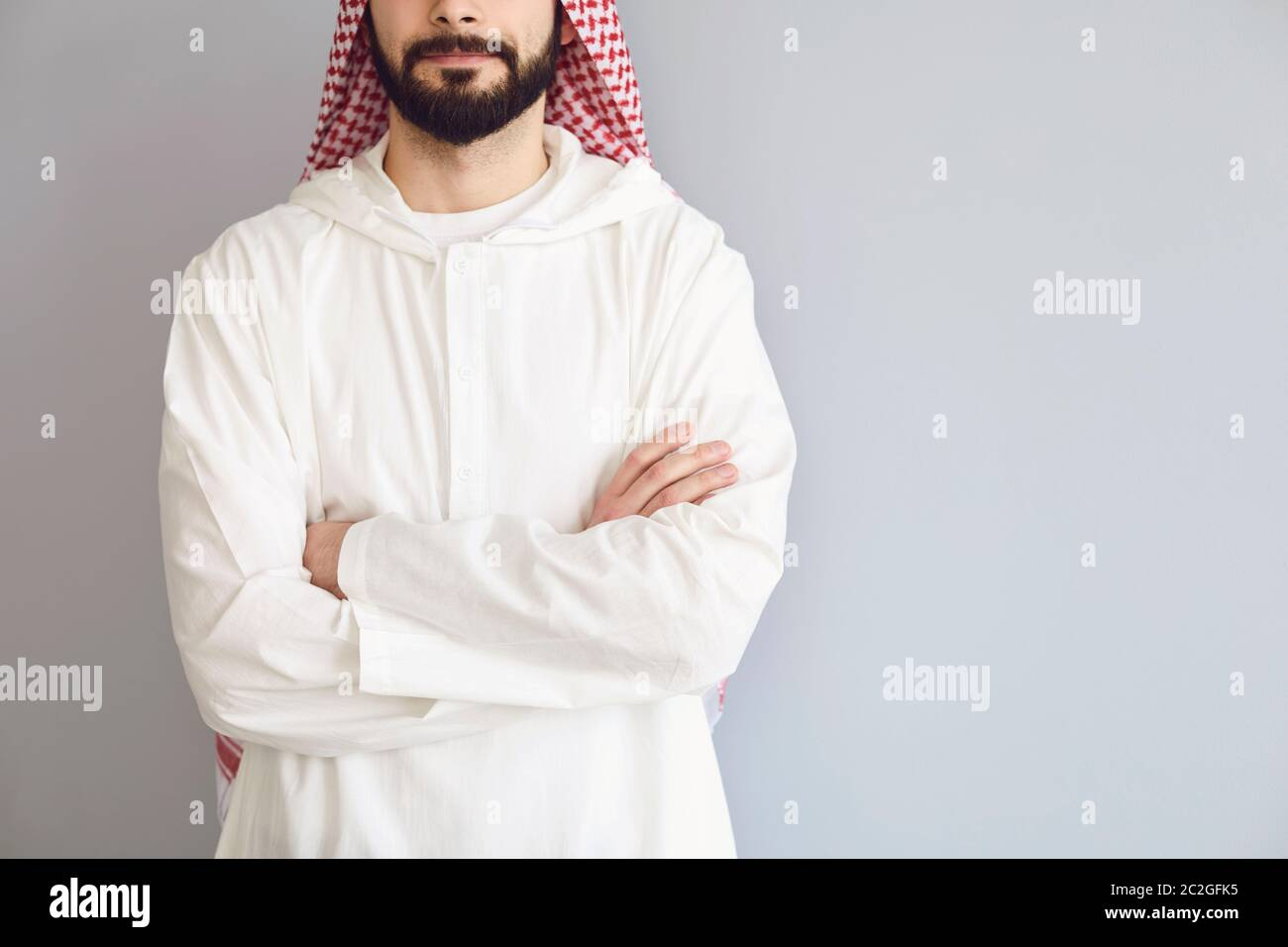 Confident arabic man faceless crossed his arms on a gray background Stock Photo
