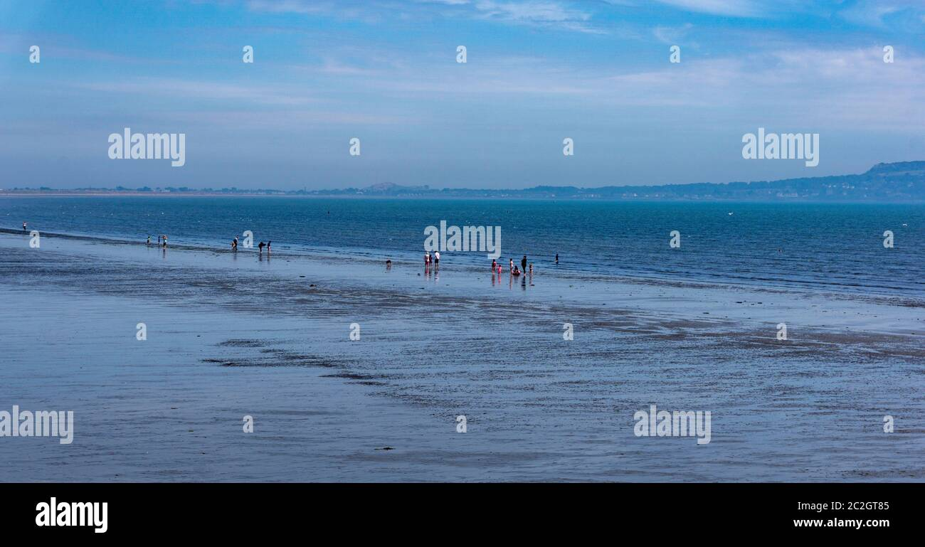 People gathered at the waters edge at Dollymount beach in Dublin, Ireland. Stock Photo