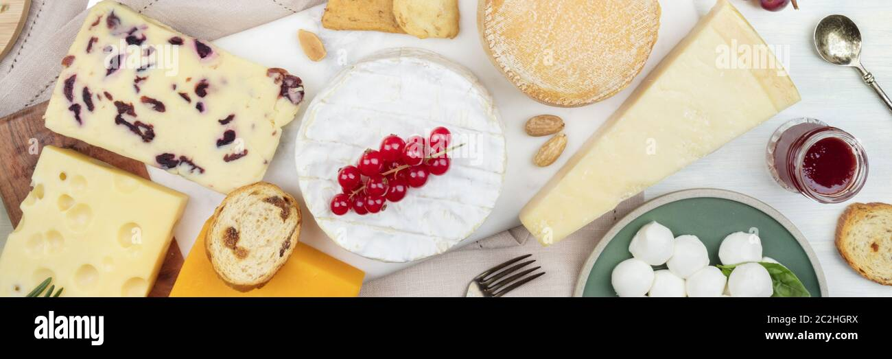 A panorama of cheeses, shot from the top. Cheese platter flat lay. Stock Photo