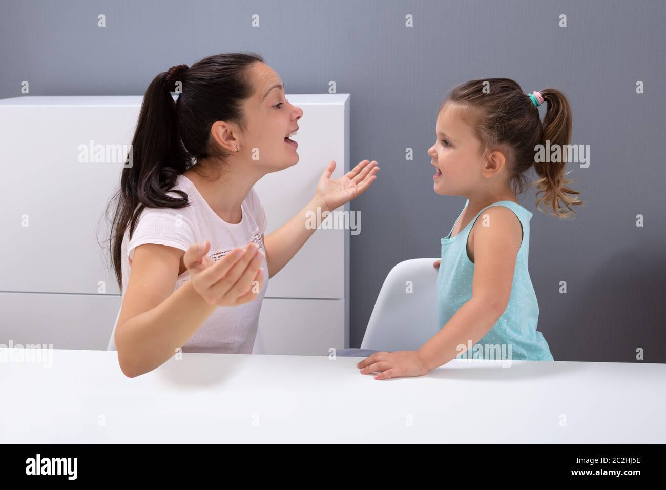 An Attractive Young Woman Helps The Girl How To Pronounce The