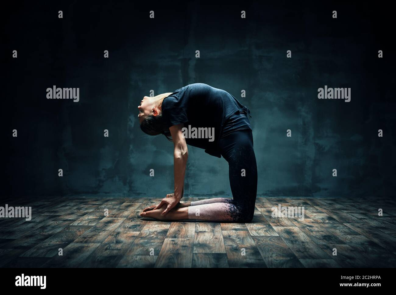 Young woman practicing yoga doing Camel pose in dark room Stock Photo