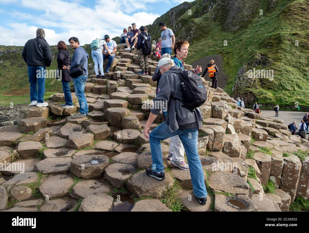 Tourists walking over geometrical basalt columns rock formations at Giant's Causeway, Northern Ireland, Europe Stock Photo