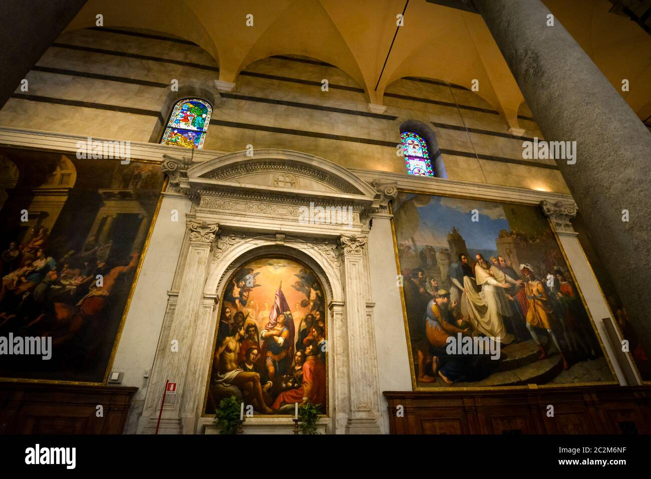 Renaissance religious paintings at the side altar of the Pisa Cathedral in Pisa Italy showing the gothic interior and stained glass windows Stock Photo