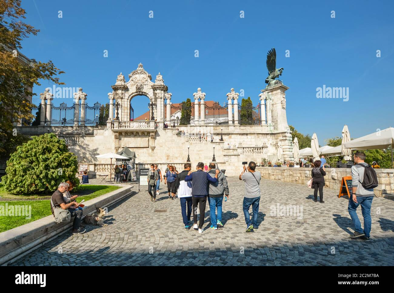 Tourists walk together and enjoy a sunny day in early autumn on the terrace overlooking the city at the Buda Castle Hill District in Budapest Hungary Stock Photo