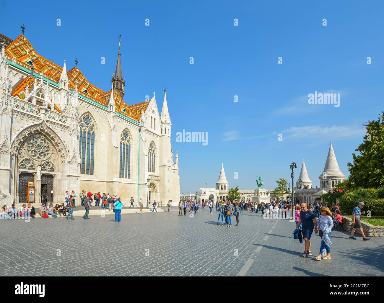 Tourists visit the Matthias Church square with the Fisherman's Bastion behind at the Buda Castle Complex in Budapest, Hungary Stock Photo