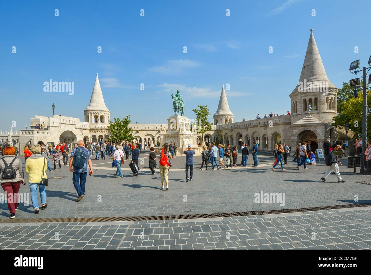 Tourists visit the Matthias Church square with the Fisherman's Bastion and statue of Saint Stephen I at the Buda Castle Complex in Budapest, Hungary Stock Photo