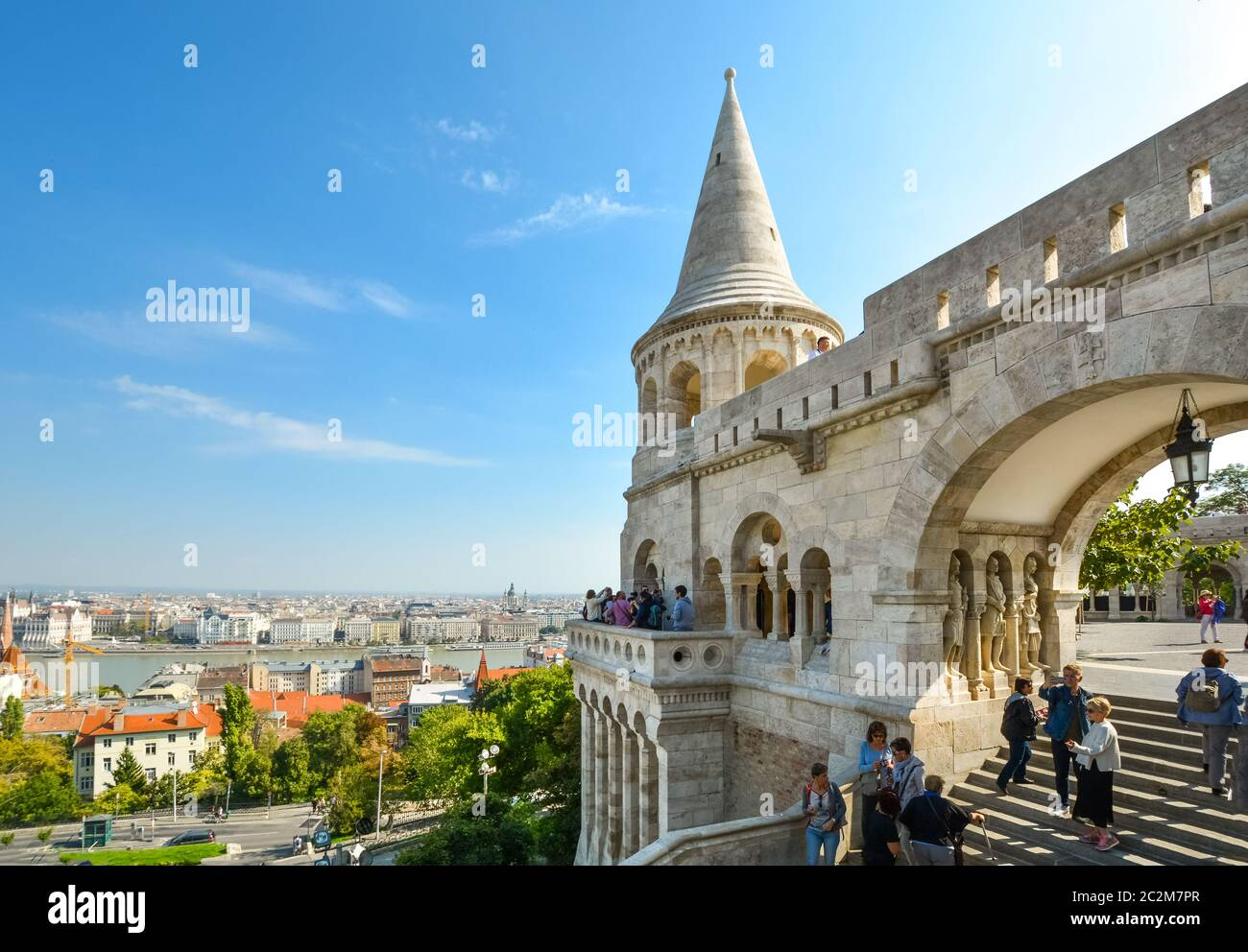 Tourists enjoy the fairy tale towers at Fisherman's Bastion overlooking the Danube River at Budapest Hungary's Castle Hill on a sunny day in autumn Stock Photo