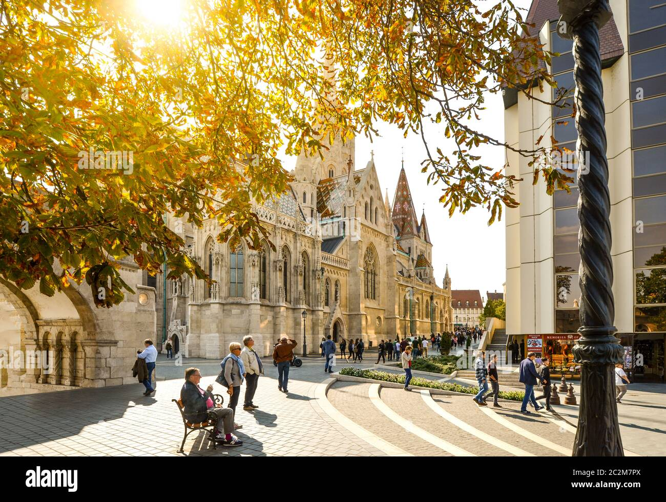 Afternoon at the Budapest Hungary Castle District standing outside the Fisherman's Bastion with Saint Matthias Church and tourists walking Stock Photo