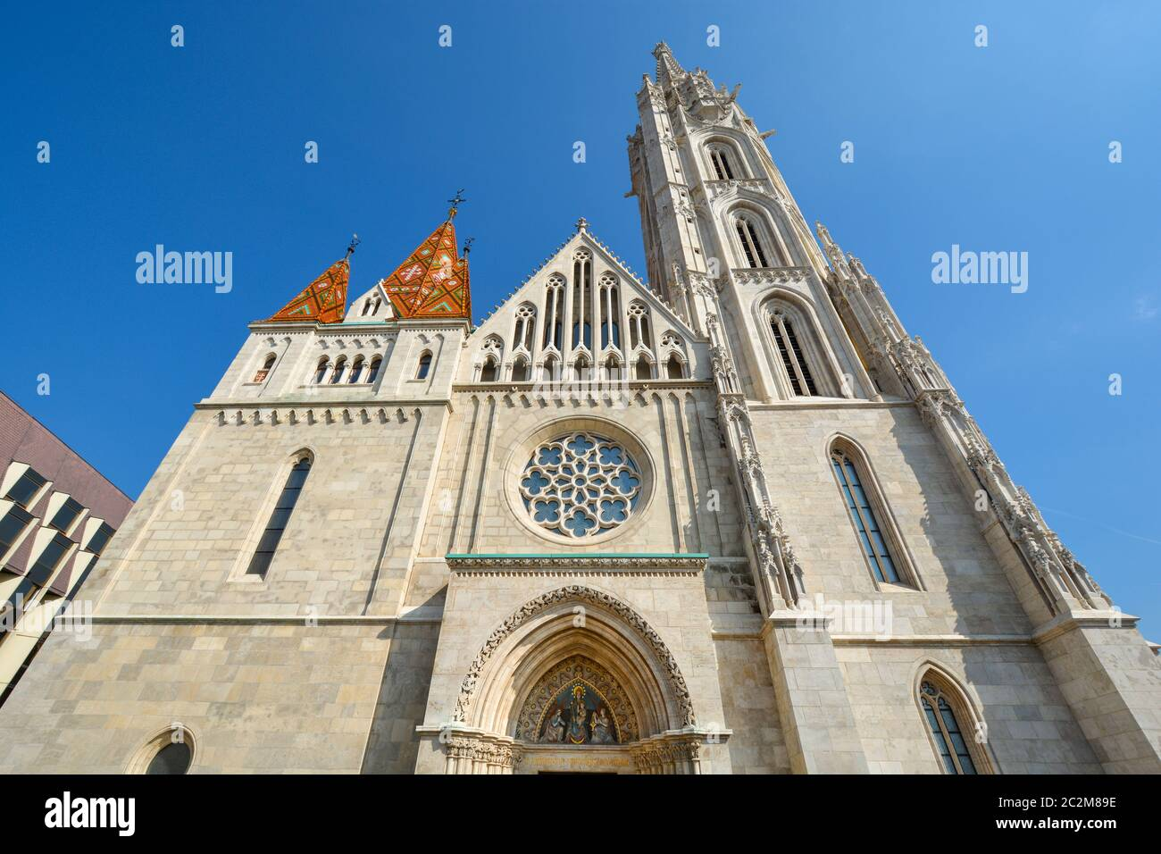The front facade and rose window of Matthias Church at Buda's Castle Complex in Budapest Hungary on a sunny day Stock Photo
