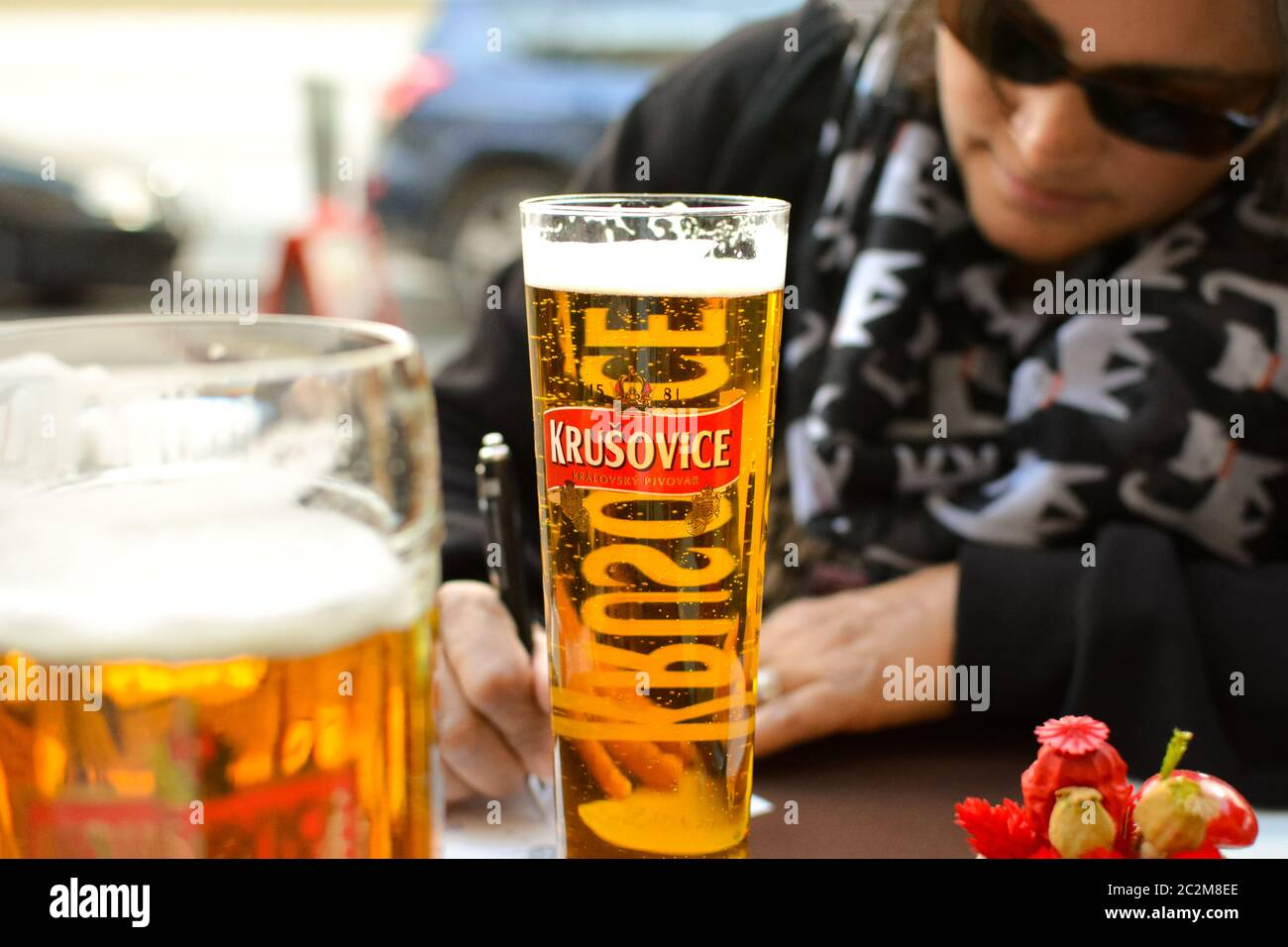 A woman wearing dark glasses and drinking a beer fills out postcards at a sidewalk cafe in Budapest Hungary. Stock Photo
