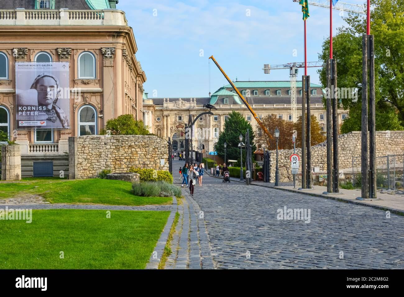 Tourists including several young women leave the Royal Palace museum and art exhibit, part of the Buda Castle Complex in Budapest, Hungary Stock Photo