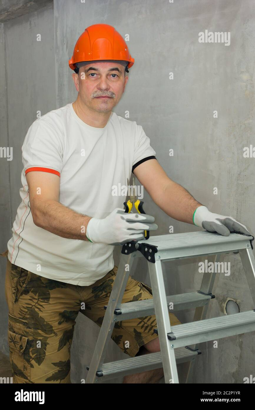Electrician with a tool and stepladder Stock Photo