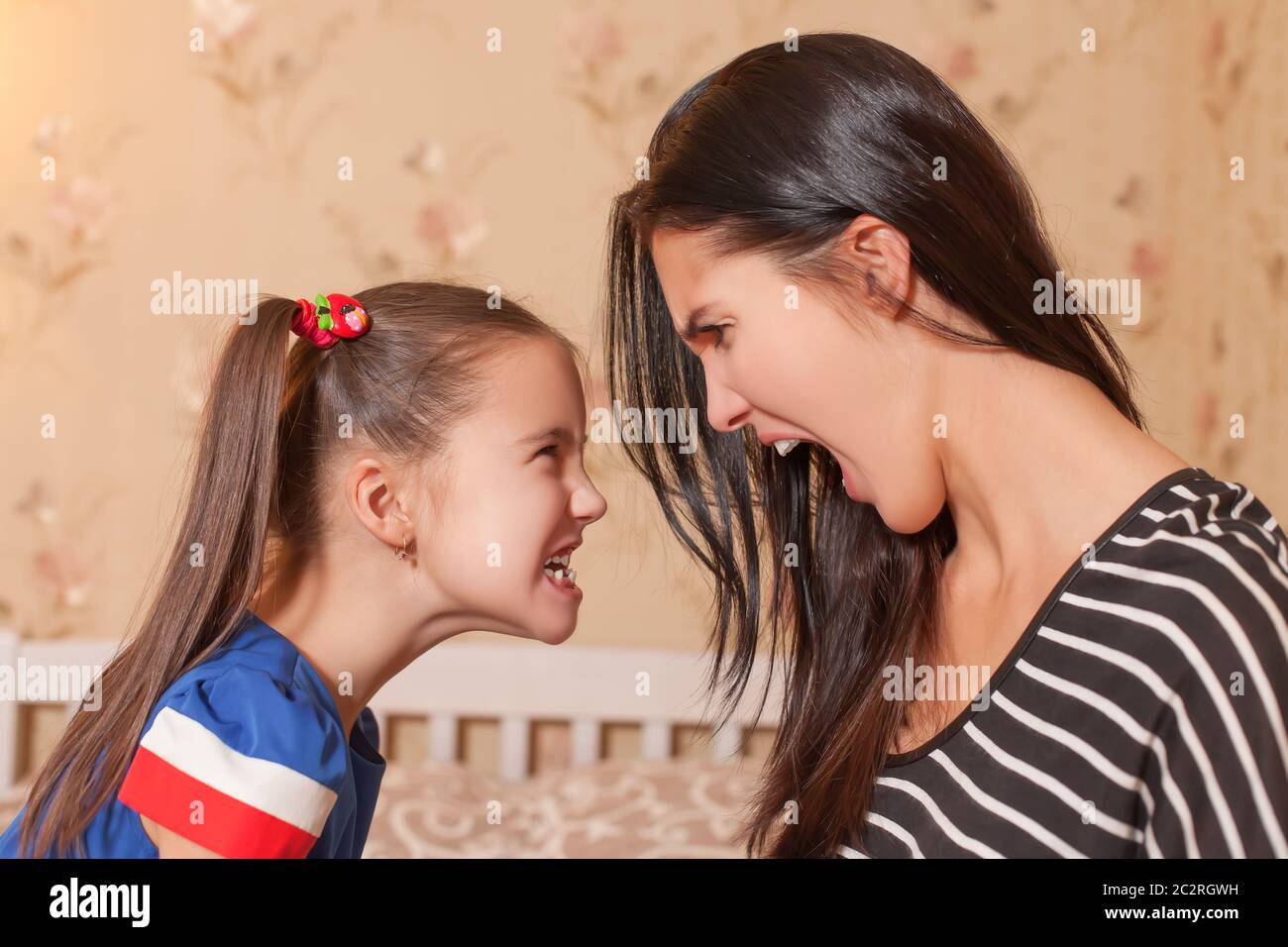 Young mother and her little daughter make each other terrible faces Stock Photo