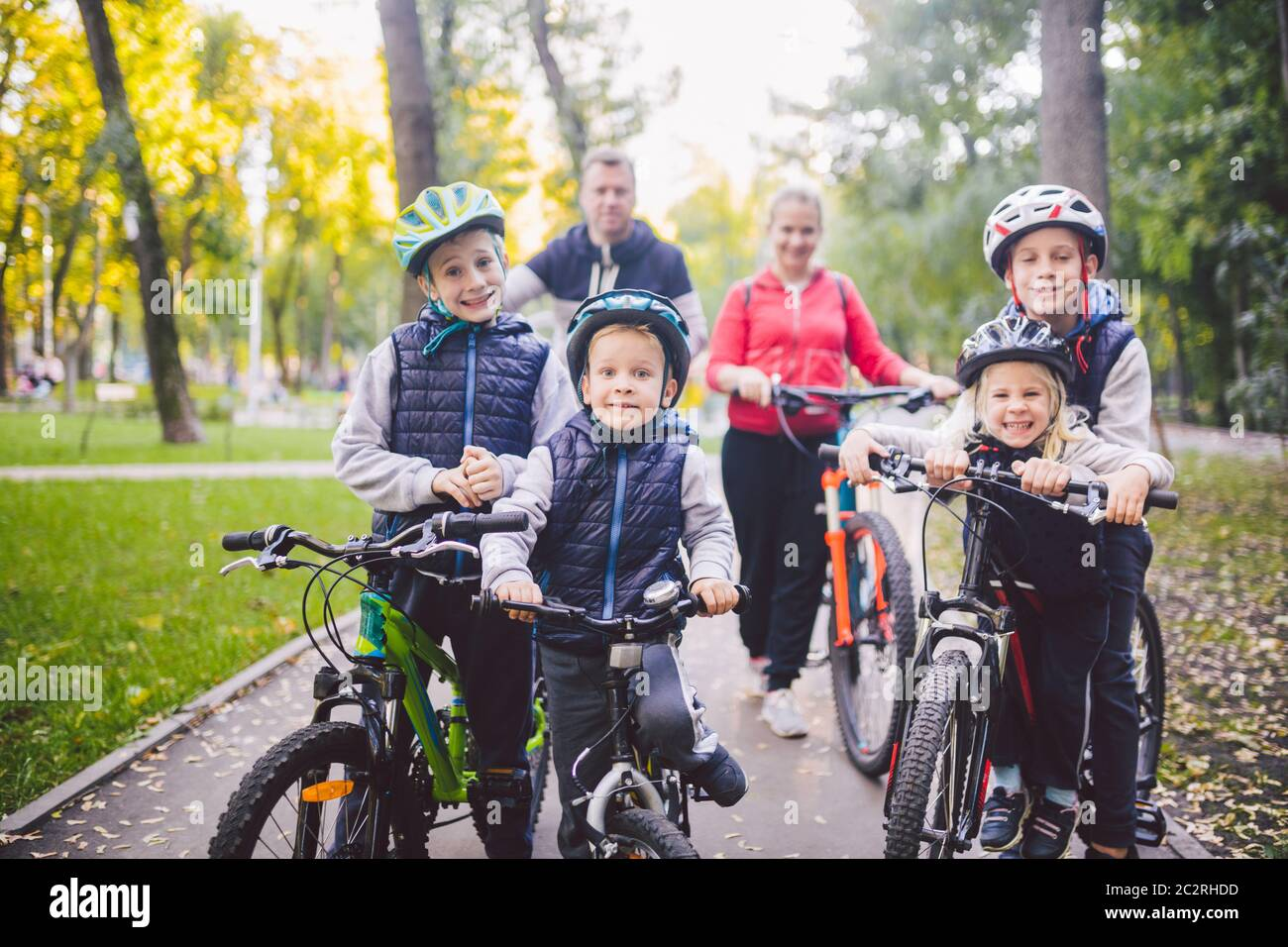 Theme family sports vacation in park in nature. big friendly Caucasian family of six people mountain bike riding in forest. Chil Stock Photo