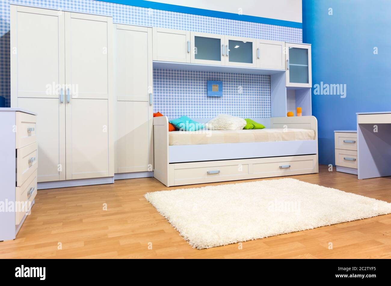 Bright Child S Bedroom With A Bed With Colorful Pillows And Cupboard Stock Photo Alamy