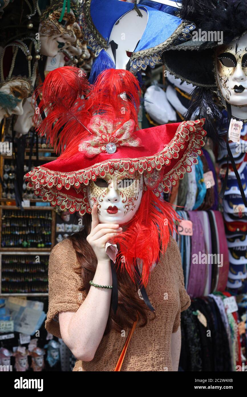 Girl wearing a Carnival Mask at shop stall in Venice Italy Stock Photo