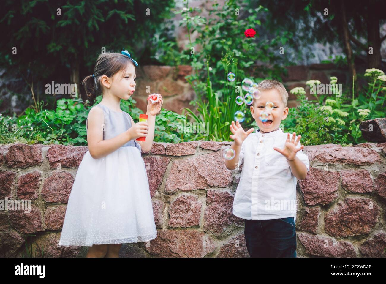 Two children in the park blowing soap bubbles and having fun. Two baby Playing With Soap Bubbles. brother and sister having fun Stock Photo