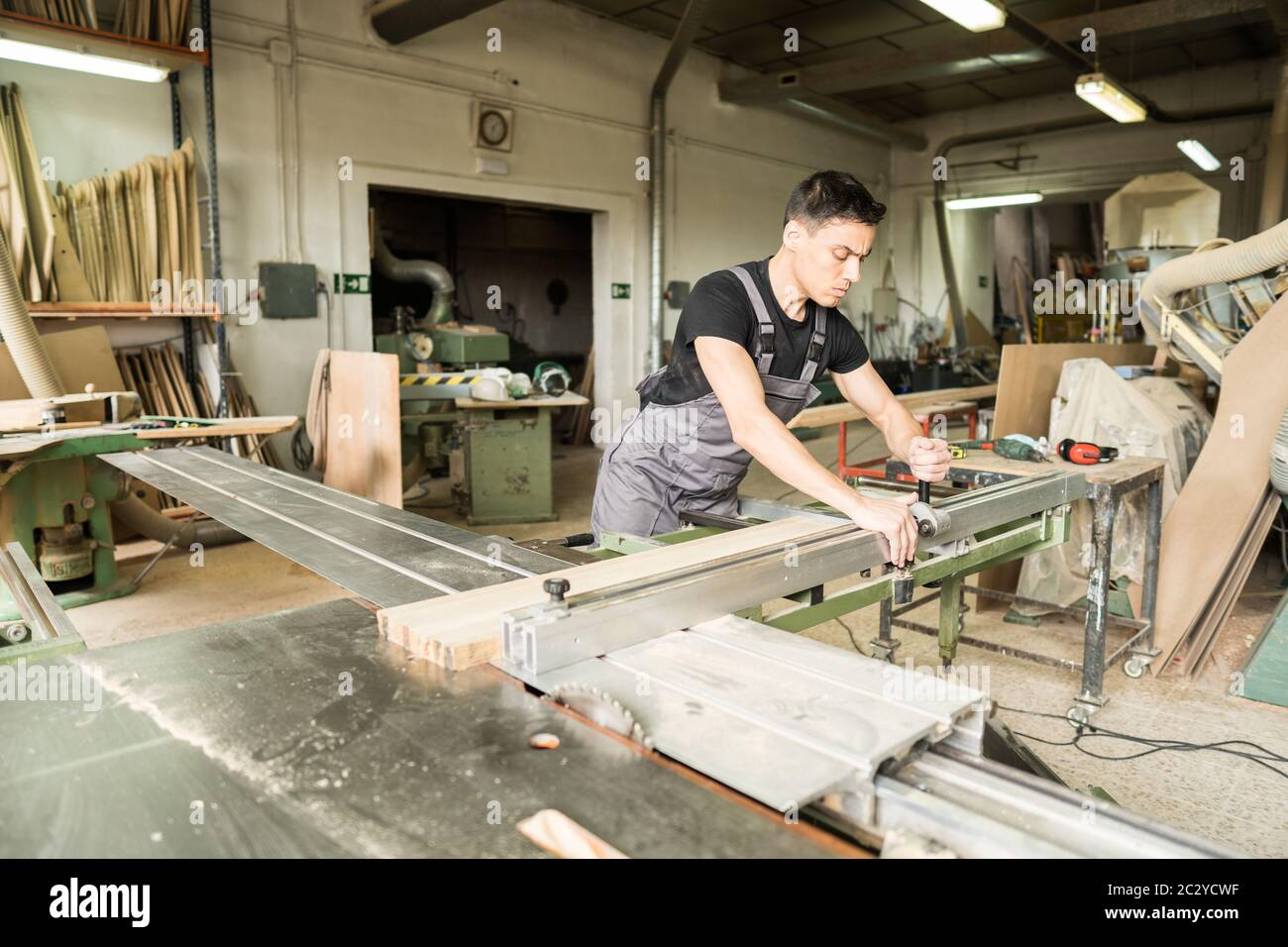 Worker cutting on a sliding table saw in a factory. Mid shot. Stock Photo
