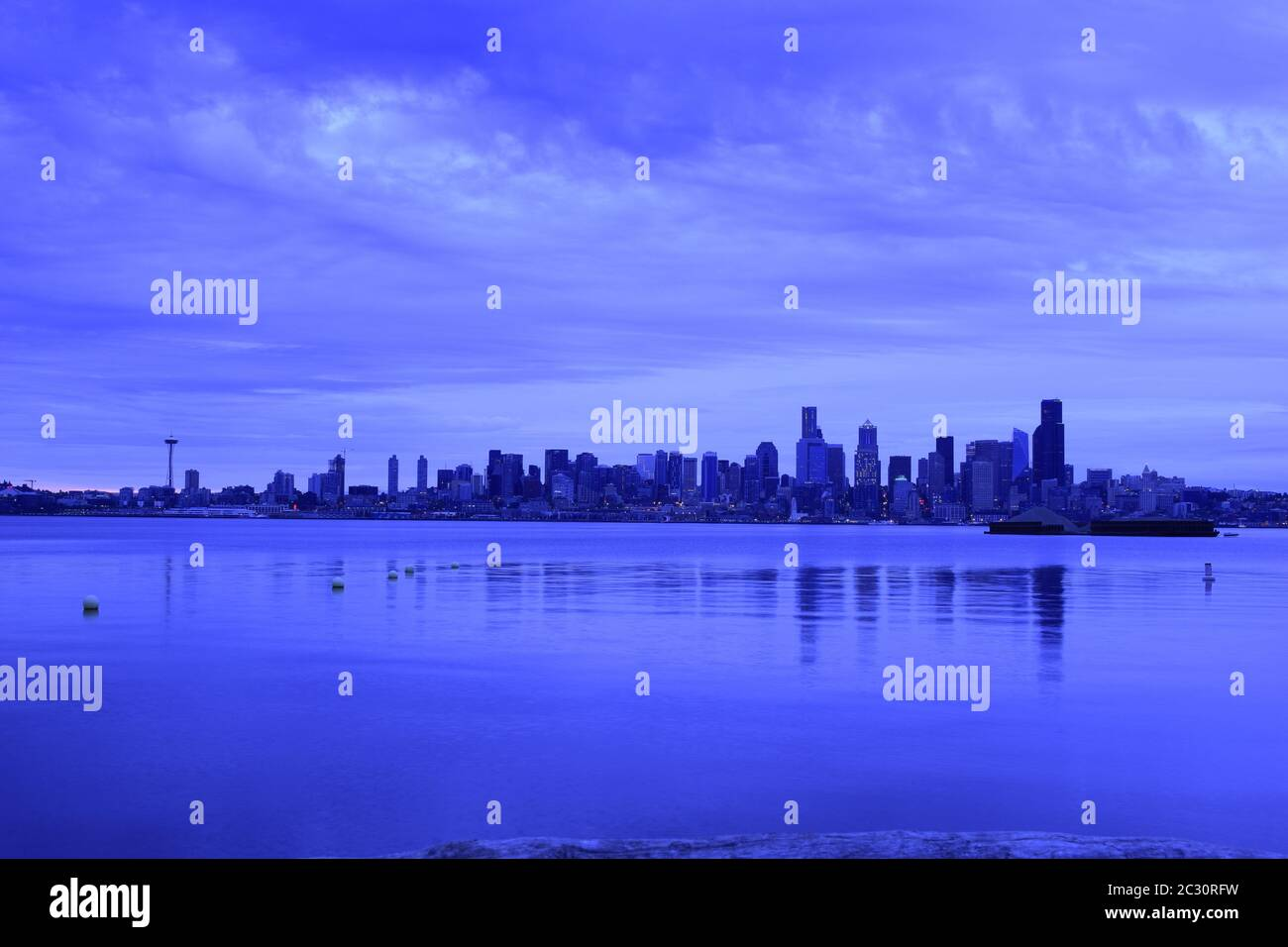 Iconic Seattle Skyline From Across The Puget Sound During A Dramatically Cloudy Dawn Stock Photo