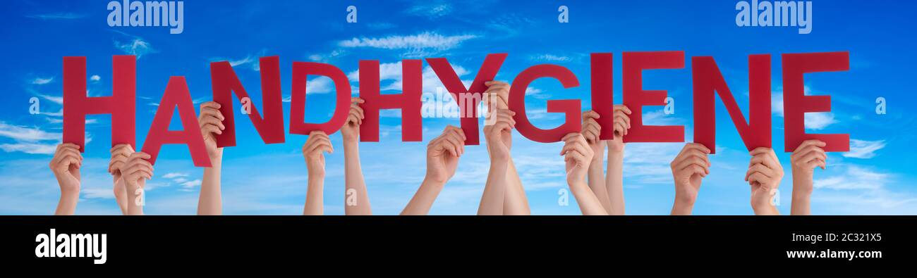 People Hands Holding Red German Word Handhygiene Means Hand Hygiene. Blue Sky As Background Stock Photo