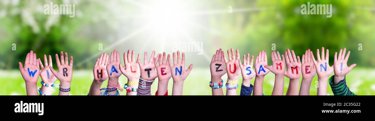 Children Hands Building Colorful German Word Wir Halten Zusammen Means Together We Are Stron. Sunny Green Grass Meadow As Background Stock Photo
