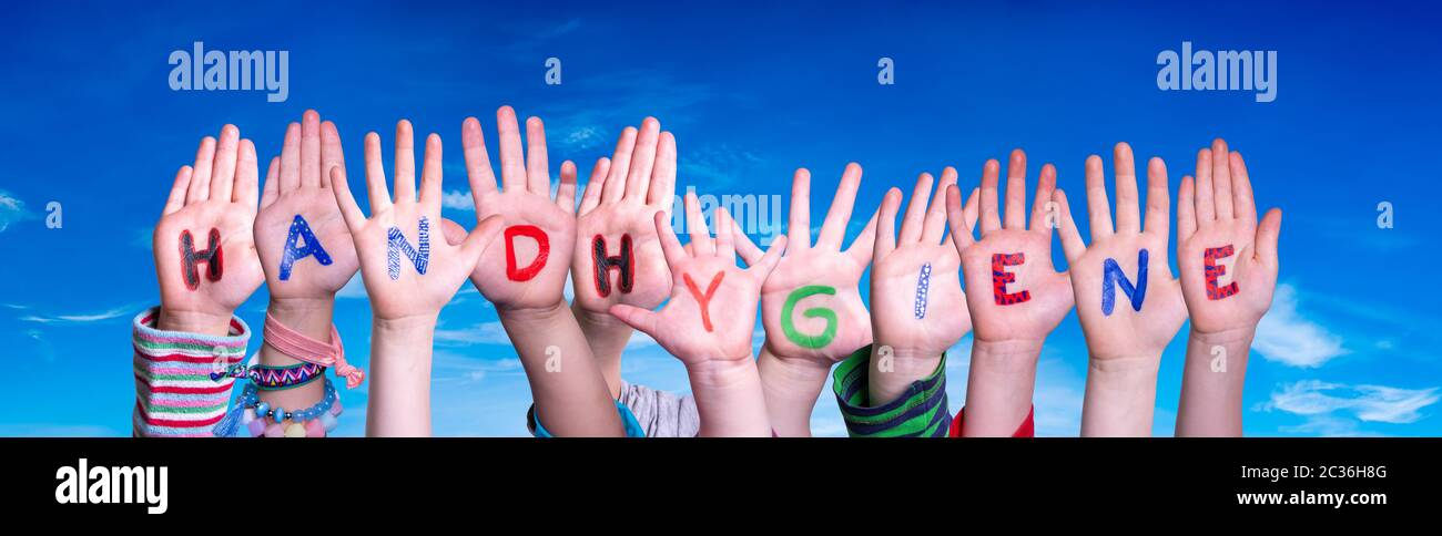 Kids Hands Holding Colorful German Word Handhygiene Means Hand Hygiene. Blue Sky As Background Stock Photo