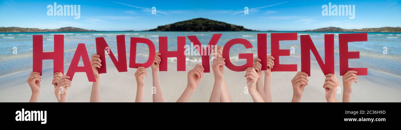 People Hands Holding Red German Word Handhygiene Means Hand Hygiene. Ocean And Beach As Background Stock Photo