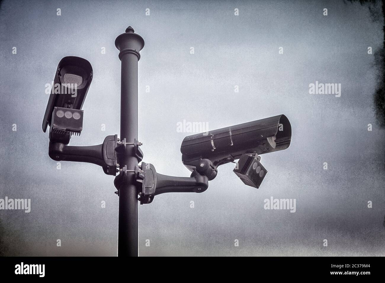Two CCTV security cameras mounted on a pole in street. Stock Photo