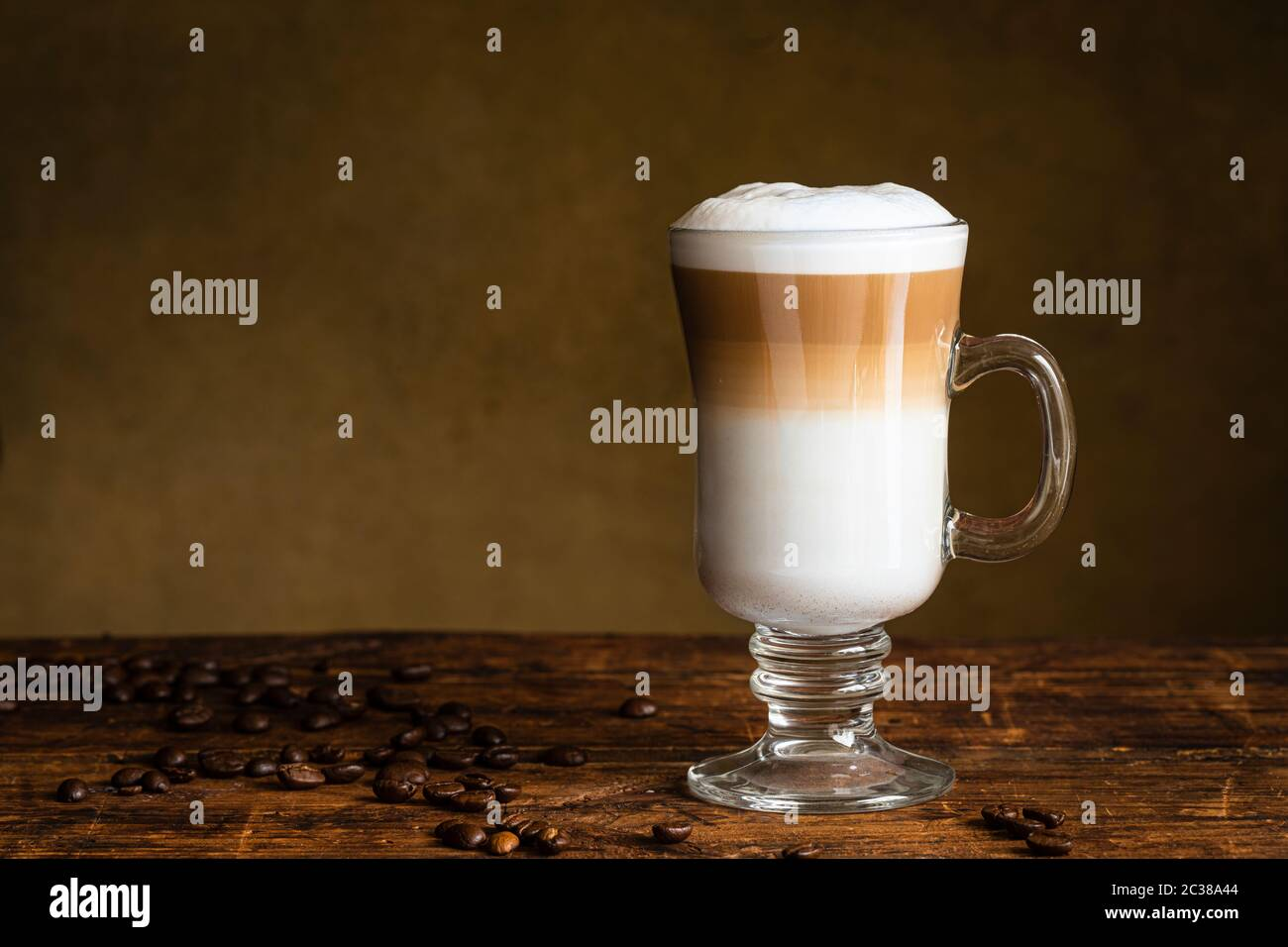 Cafe Latte Macchiato Layered Coffee In A See Through Glass Irish Coffee Glass The Cup Is On A Wooden Table With Coffee Beans On The Table Next To The Stock Photo