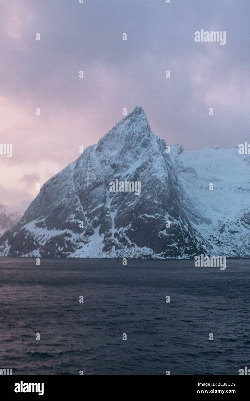 A pink sunset over the iconic Olstinden in Norway. Stock Photo