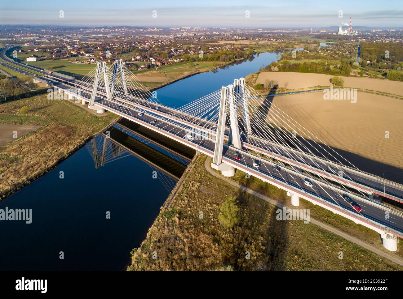 New modern double cable-stayed bridge with wide three-lane roads over Vistula River in Krakow, Poland, and its reflection in water at sunrise. Part of Stock Photo