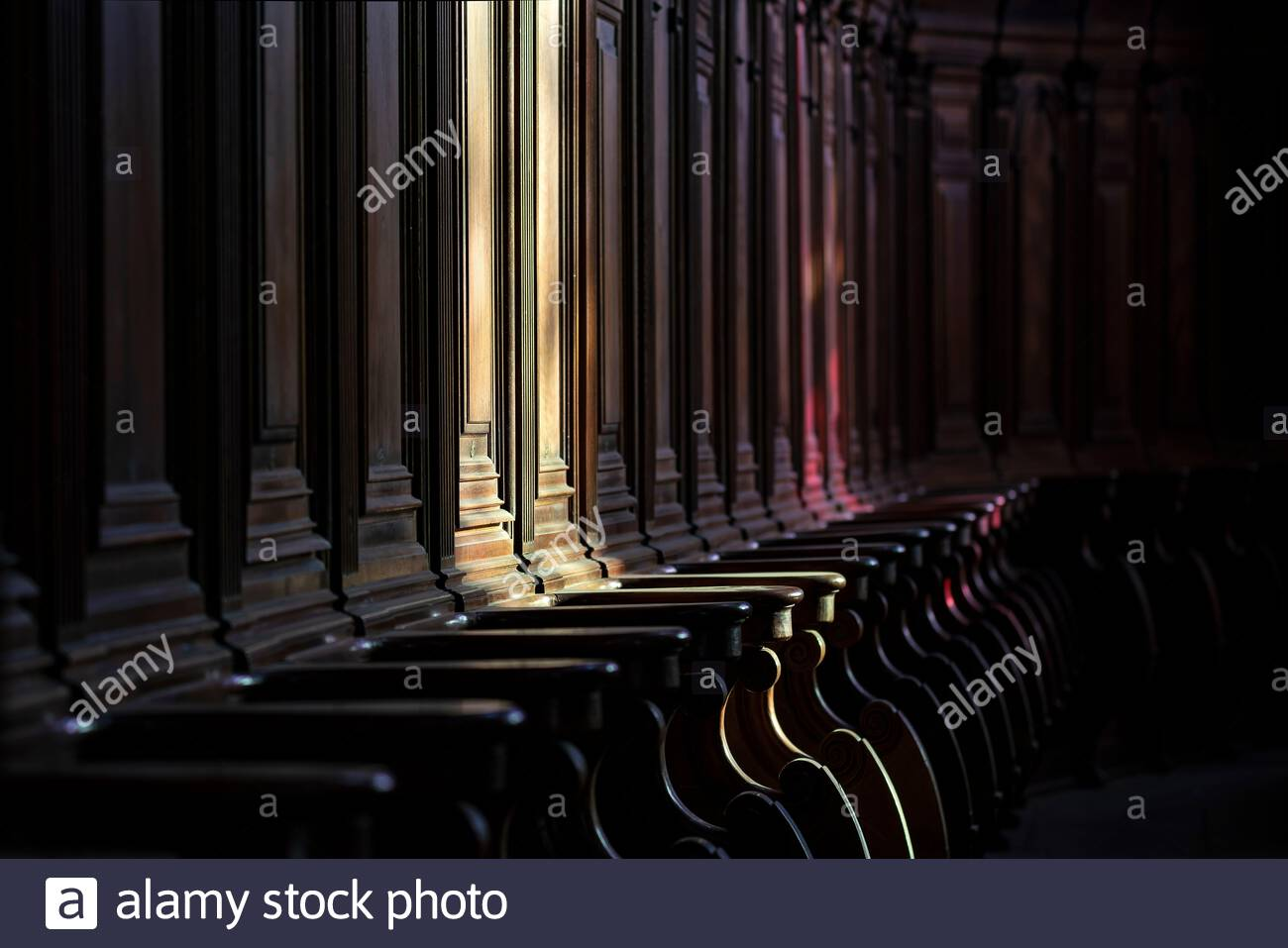 Sunlight coming through stained glass pointing to an empty seat in the ambulatory of a church illustrating the priest shortage in the Catholic Church Stock Photo