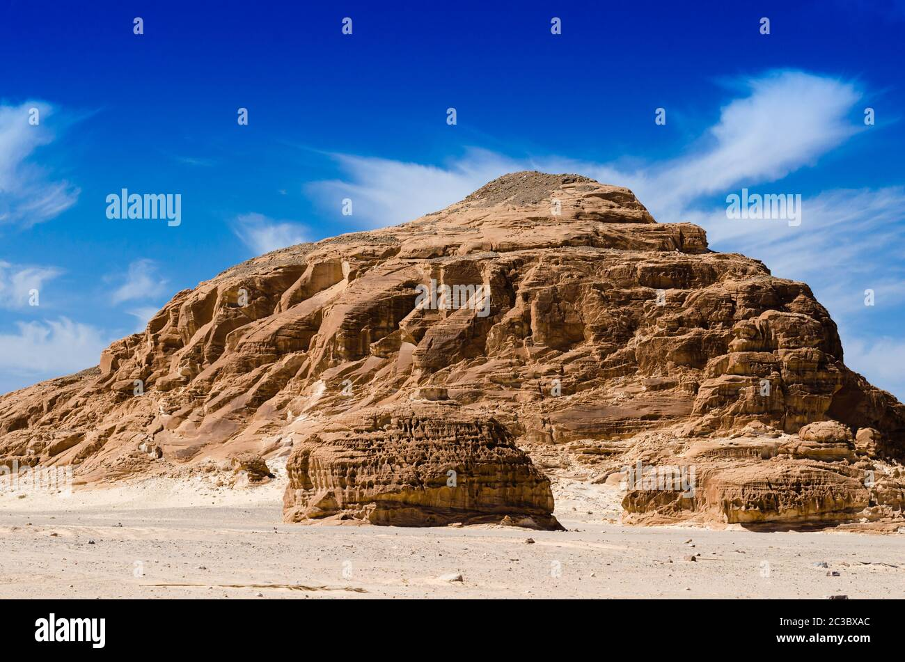 high rocky mountains against the blue sky and white clouds in the desert in Egypt Dahab South Sinai Stock Photo