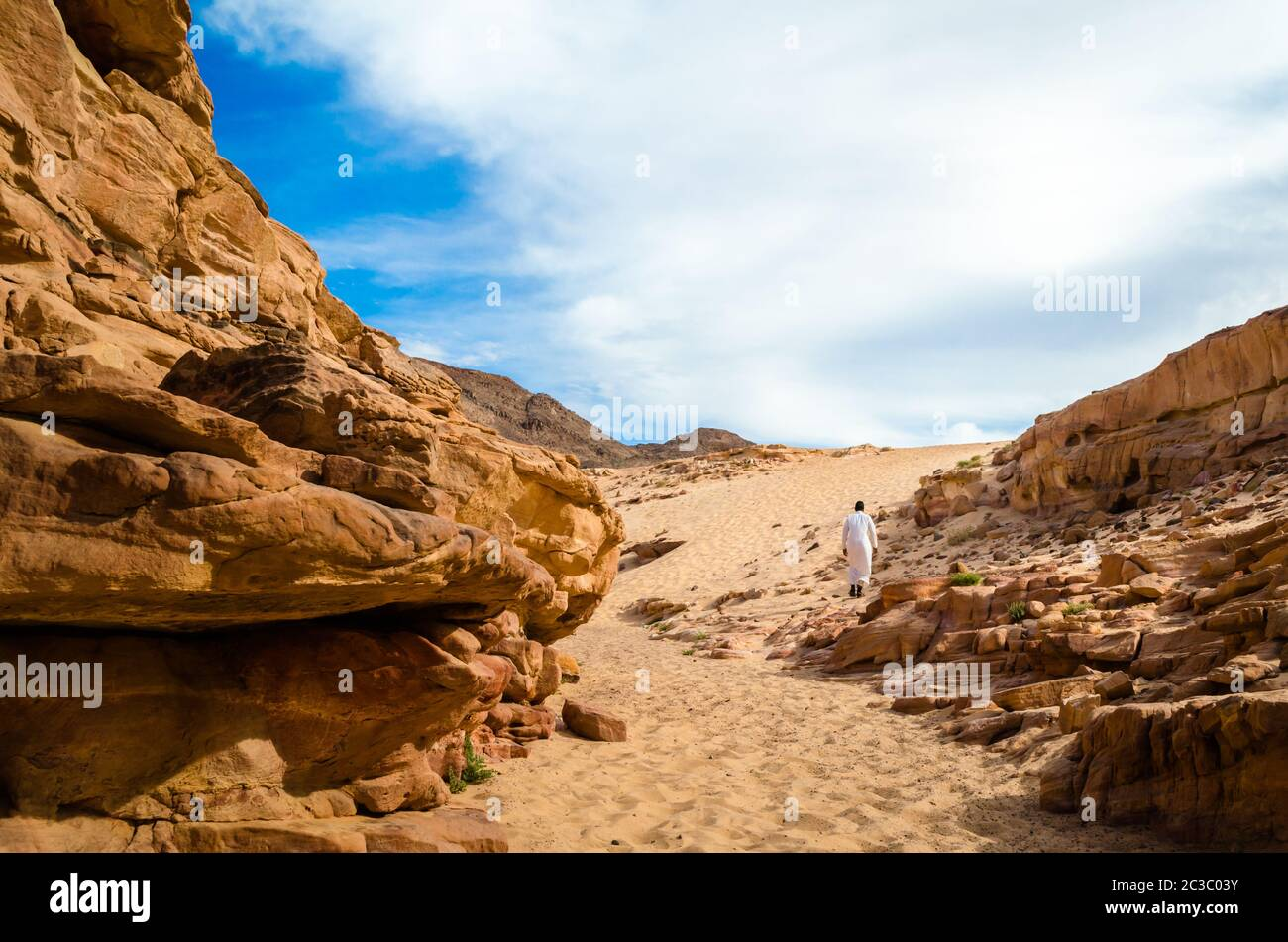 man in white arab clothing walks in a colored canyon in Egypt Dahab South Sinai Stock Photo