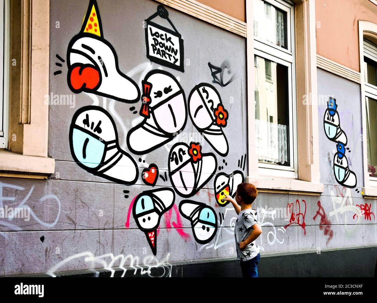 Dortmund, Germany, June 19th, 2020: Mask worms. Since the outbreak of the corona crisis in March 2020, small corona virus graffiti with a mouth mask created by an unknown sprayer can be seen on many house walls in Dortmund.   ---   Dortmund, 19.06.2020: Maskenwürmchen. Seit Ausbruch der Corona-Krise im März 2020 sind kleine Coronaviren-Graffitis mit Mundschutz eines unbekannten Sprayers an vielen Hauswänden in Dortmund zu sehen. Stock Photo